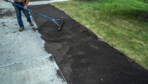 Landscaper Applying Top Soil On Yard