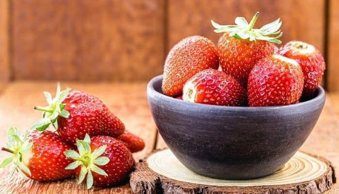 A rustic scene with Albion strawberries in a wood bowl and on a table.