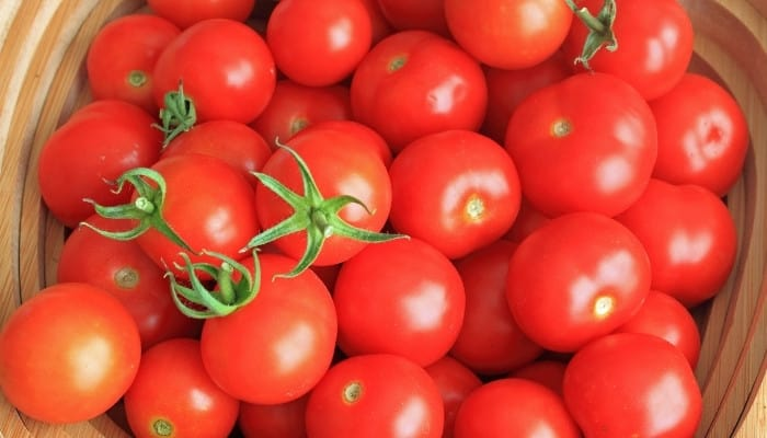 A basket full of red, ripe cherry tomatoes.
