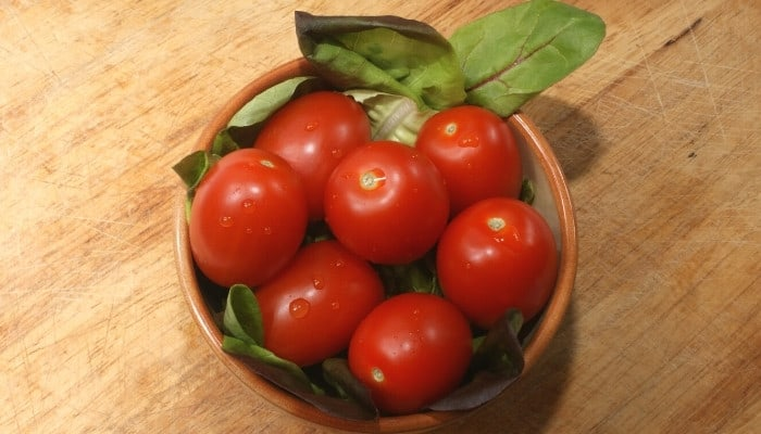 A bowl of organic plum tomatoes and salad leaves on a wood table.