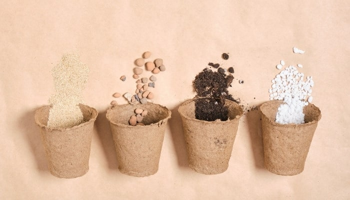 Four peat pots: one with vermiculite, one with clay balls, one with ground bark, and one with perlite set against a peach-colored background.