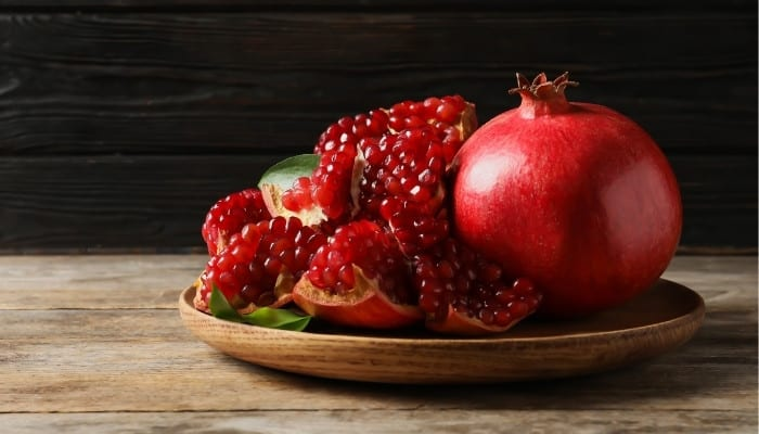 A whole pomegranate sitting beside an opened pomegranate on a rustic wood table against a dark wall.