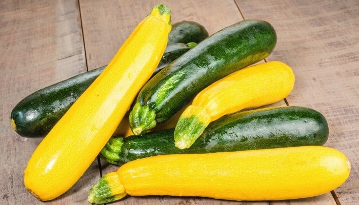 A pile of zucchini and yellow summer squash on a wood table.
