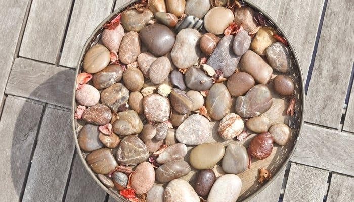 A round pebble tray on wood deck.